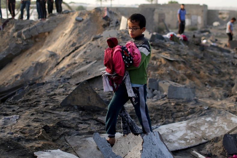 a_palestinian_boy_carries_belongings_retrieved_from_a_house_destroyed_in_an_israeli_air_strike_in_the_southern_gaza_strip_november_13x_2019_