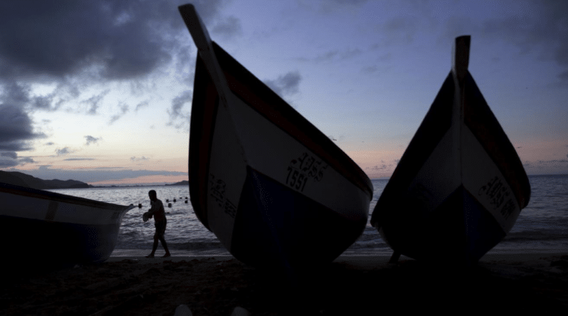 A man walks past wooden boats in the bay of Rio Caribe a town near caribbean islands, in the eastern state of Sucre, Venezuela October 29, 2015. REUTERS/Carlos Garcia Rawlins