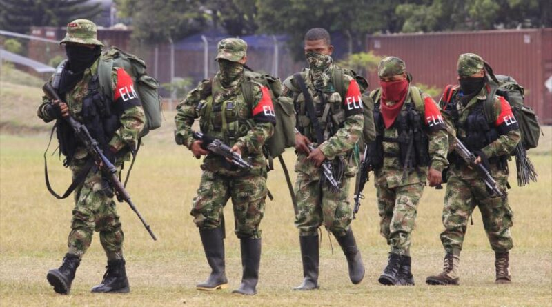 Members of the Colombian guerrilla ELN walk to a military base to hand over their weapons.