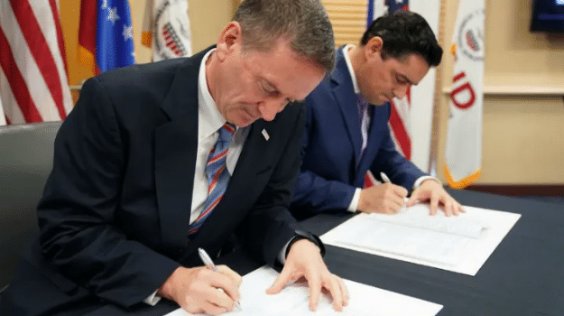 "Featured image: U.S. Agency for International Development Administrator Mark Green with Carlos Vecchio, Venezuelan fake ambassador to the United States at the signing of their ""deal"". Photo by: Mark Green via Twitter."