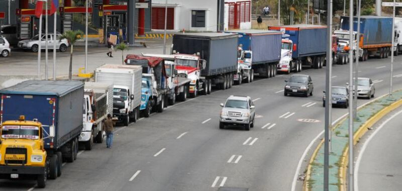 Featured image: Long lines of trucks waiting to load their tanks with fuel and adding to the long lines of cars that are still visible all over Venezuela due to the scarcity created since 2020 as a direct result of US blockade.