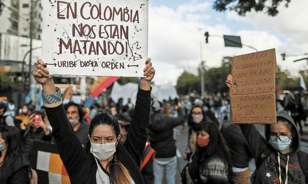 """Featured image: Protester in Colombia holding a banner that reads: """"In Colombia they are killing us, Uribe gave the order."""" Photo courtesy of RedRadioVe."""