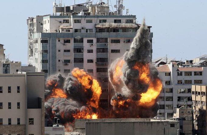 Featured image: An international media building destroy by Israel military in Gaza. Al Jazeera and AP offices operated from this building. The only possible reason behind the bombing is the sudden and recent fair coverage from the Qatari news outlet about the atrocities of Israel against Palestinians. A ball of fire erupts from the Jala Tower as it is destroyed in an Israeli air strike. Picture: Mahmud Hams/AFP