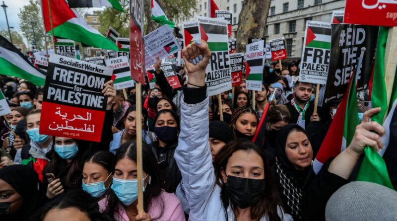 """Demonstrators hold banners and placards outside Downing Street during a """"Save Sheikh Jarrah"""" demonstration in London on Tuesday, May 11, 2021. At least 24 Palestinians were killed Monday, May 10 in Israeli air raids on Gaza Strip. (Photo: Vudi Xhymshiti/Anadolu Agency via Getty Images)"""