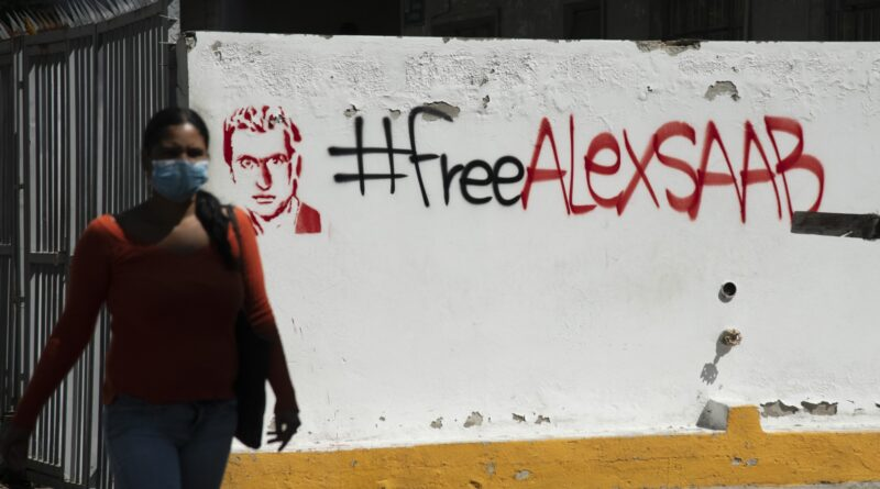 """A pedestrian passes in front of """"Free Alex Saab"""" graffiti """" in Caracas, on Feb. 4. Photographer: Carlos Becerra/Bloomberg."""