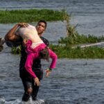Young Venezuelan (Cesar Padron) helping and older woman to cross the Rio Grande, a photo used to magnify Venezuela's migration issue. File photo.