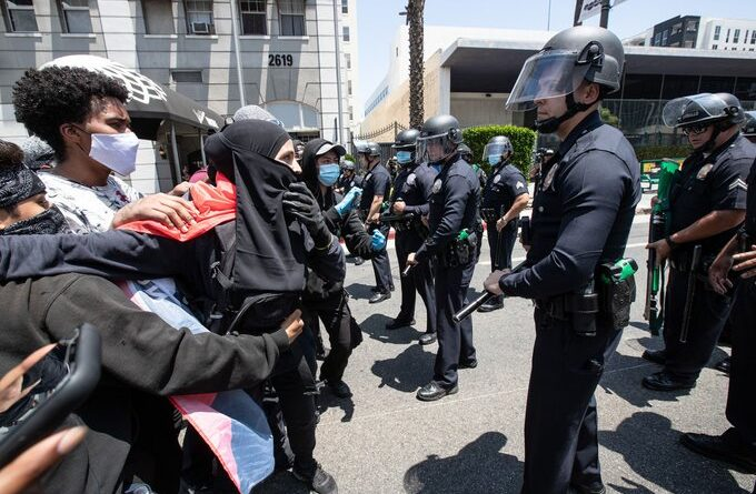 Police in full gear in front of a small peaceful protest defending transgender people rights in LA, California. Photo courtesy of the New York Post.