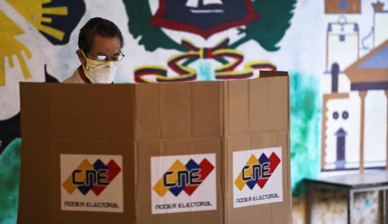 A man stands at a voting booth at a polling station during parliamentary election in Caracas, Venezuela, December 6, 2020 [Manaure Quintero/Reuters]