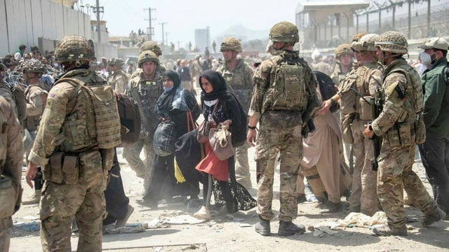 Two Afghan women walking near Kabul's airport surrounded by US soldiers. Photo: Telesur / Getty Images.
