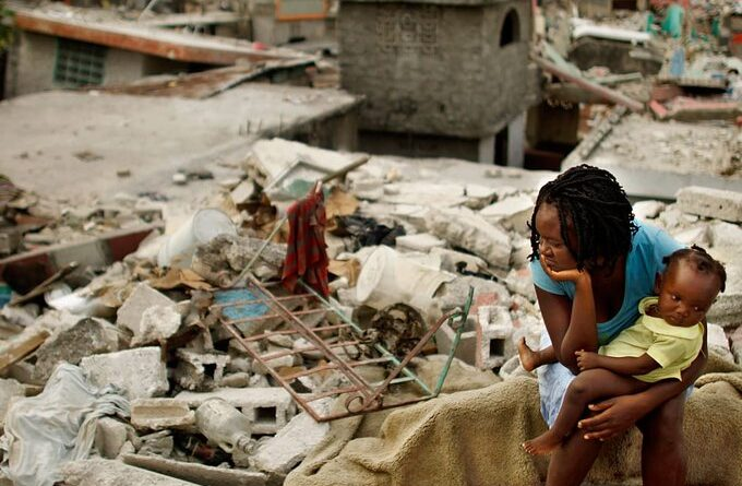 Haitian woman with a baby in her lap seating over earthquake rubble. Photo by Twitter /@KhaledBeydoun .