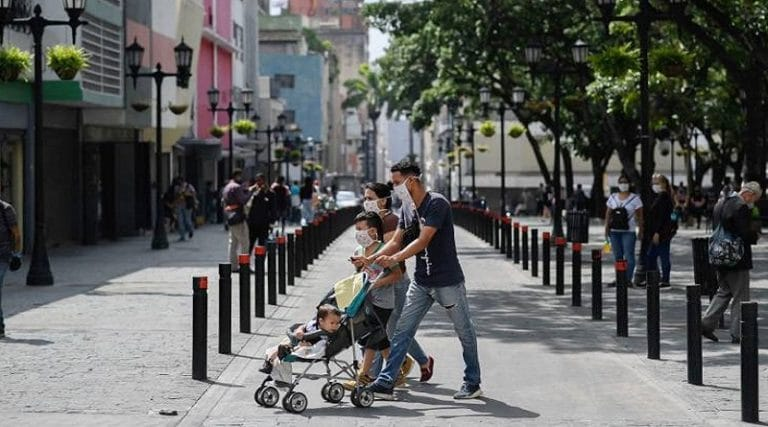 A Venezuelan family walking in downtown Caracas, all wearing their face masks. File photo.