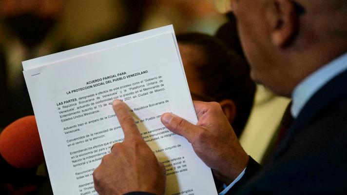 The head of the Venezuelan government delegation, Jorge Rodríguez, shows the document of the partial agreement for the social protection of the Venezuelan people (Photo: Pedro Pardo / AFP).