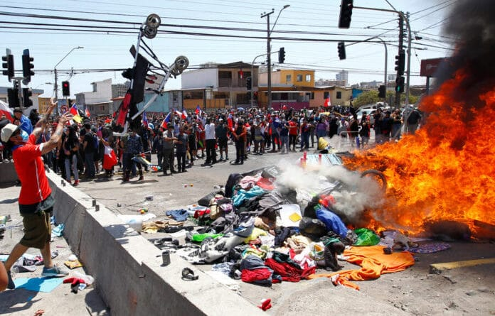 Chileans burning the few belongings of Venezuelan migrants and launching a baby stroller to the fire. Photo courtesy of Twitter.