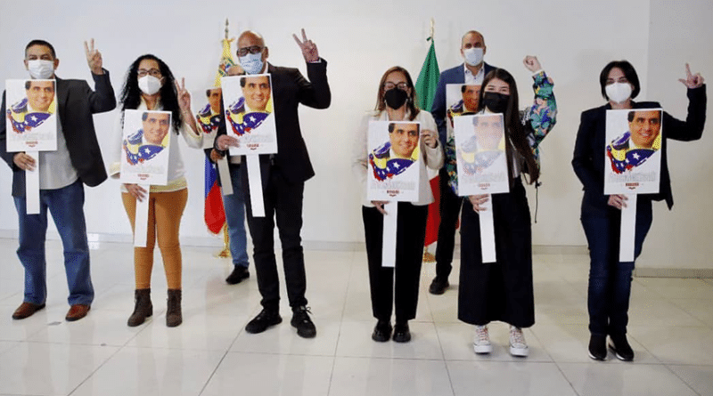 Jorge Rodriguez surrounded by the rest of the Venezuelan government delegation to the Mexico Talks, all holding an image of the Venezuelan diplomat Alex Saab who was kidnapped by the Cape Verdean government following an unsubstantiated extradition request from the United States. Photo courtesy of Twitter / @jorgepsuv.