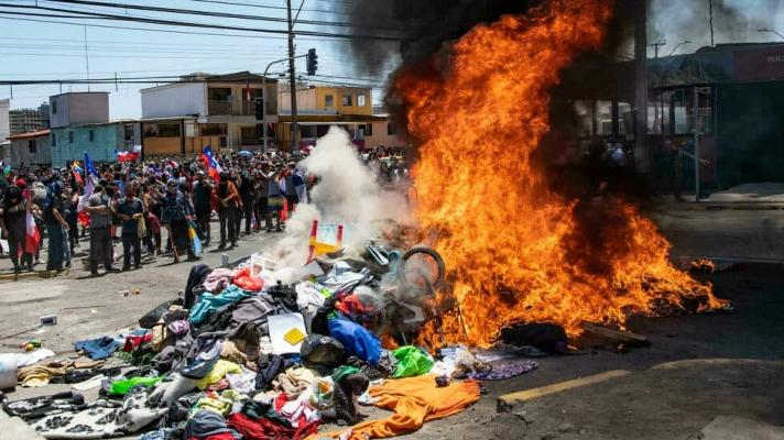 People burn tents, clothes and other belongings of Venezuelan migrants during an anti-immigration march, in Iquique, Chile, on September 25, 2021 (Photo: EFE).