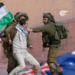 Man carrying a Palestinian flag being repressed by IDF gendarmes. Photo courtesy of Al Mayadeen English.